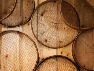 Mehlsiebe verschiedener Größe als Symbol für physikalische Filter in Sonnencreme