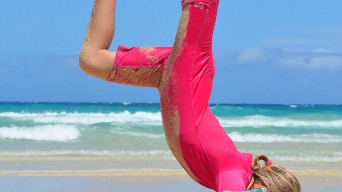 turnendes Mädchen am Strand in UV-Schutzkleidung