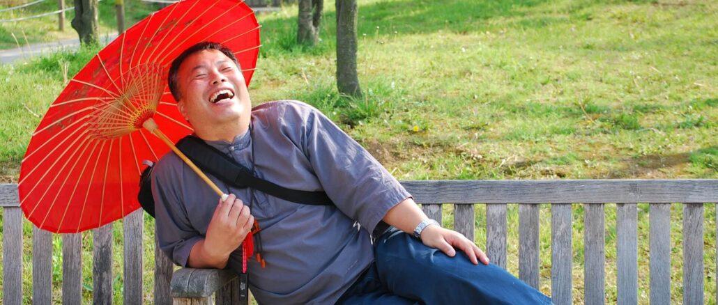 WHO-Empfehlungen: Ein lachender Mann sitzt unter einem Sonnenschirm auf einer Parkbank
