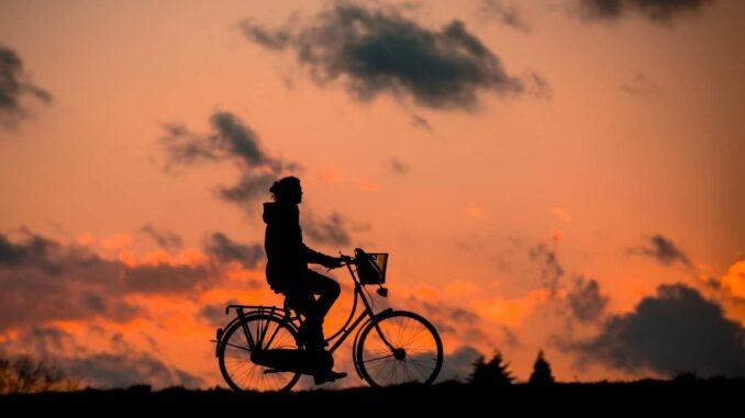 Frau auf dem Fahrrad vor Sonnenuntergang