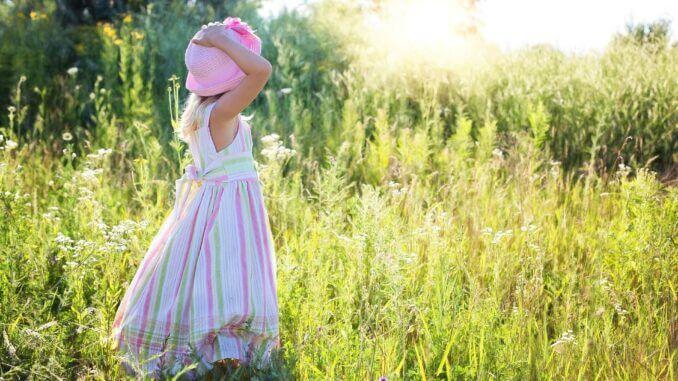 Ein Mädchen steht auf einer Sommerwiese
