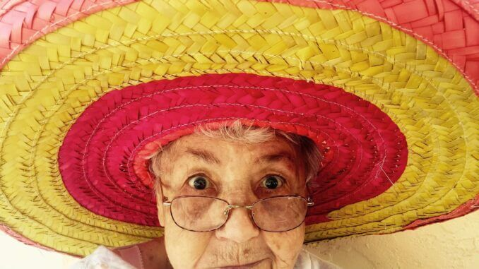 Alter Frau mit Sombrero schützt sich vor Hellem Hautkrebs